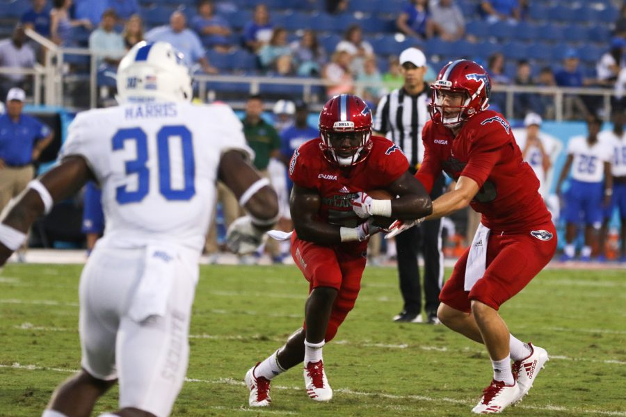 FAU redshirt junior quarterback Jason Driskel (16) passes the football off to sophomore running back Devin Singletary (5).  Joshua Giron | Staff Photographer