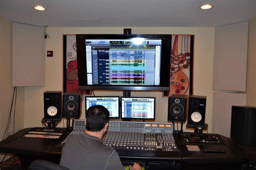 Alejandro+Sanchez-Samper%2C+faculty+supervisor+for+Hoot%2FWisdom+Recordings%2C+working+at+the+recording+studio%E2%80%99s+control+board.+Thomas+Chiles+%7C+Features+Editor