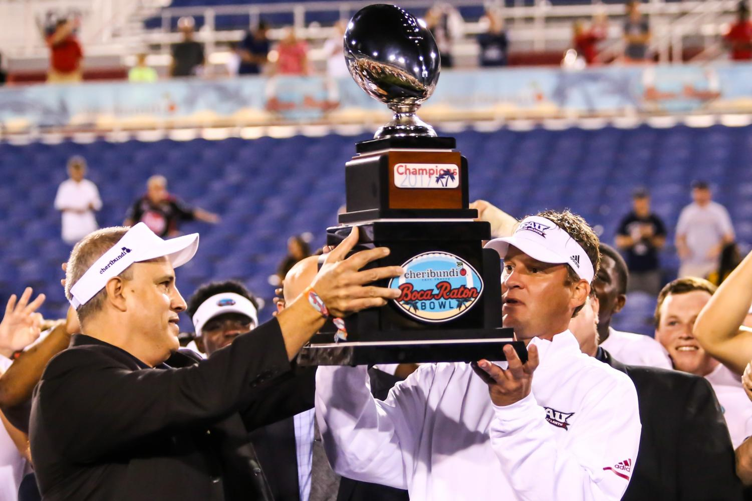 FAU head coach Lane Kiffin is handed the Cheribundi Boca Raton Bowl trophy during the trophy ceremony after FAU's 50-3 victory Saturday night. Alexander Rodriguez | Photo Editor