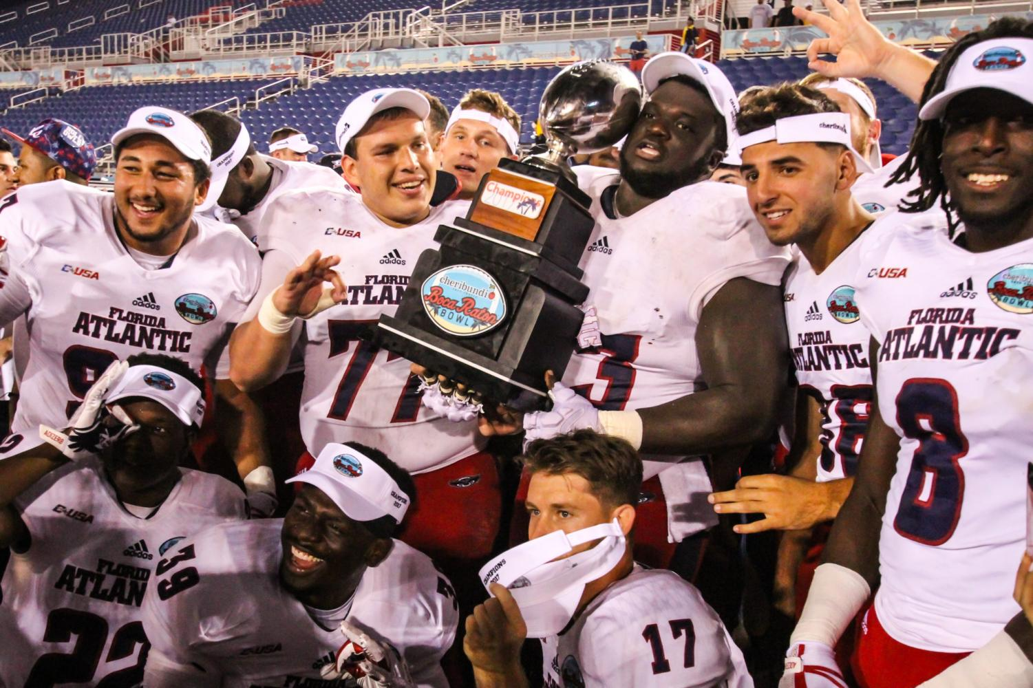 Members of the FAU Football team poses with the Cheribundi Boca Raton Bowl trophy after it was handed to them by their head coach Lane Kiffin.  Alexander Rodriguez | Senior Photographer