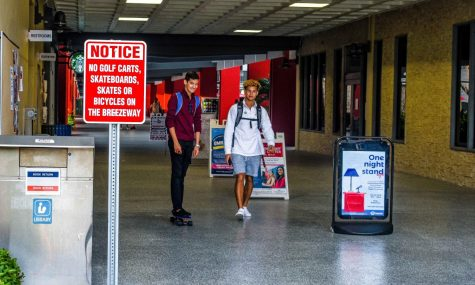 "Despite signs prohibiting skateboarding in the Breezeway, a student rides his board toward the entrance near the food court. Anthony ""Joe"" Washko 