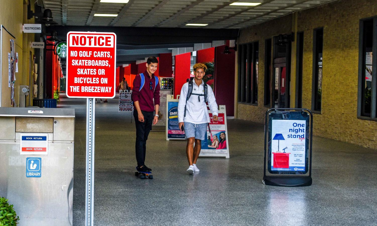 Despite signs prohibiting skateboarding in the Breezeway, a student rides his board toward the entrance near the food court. Anthony