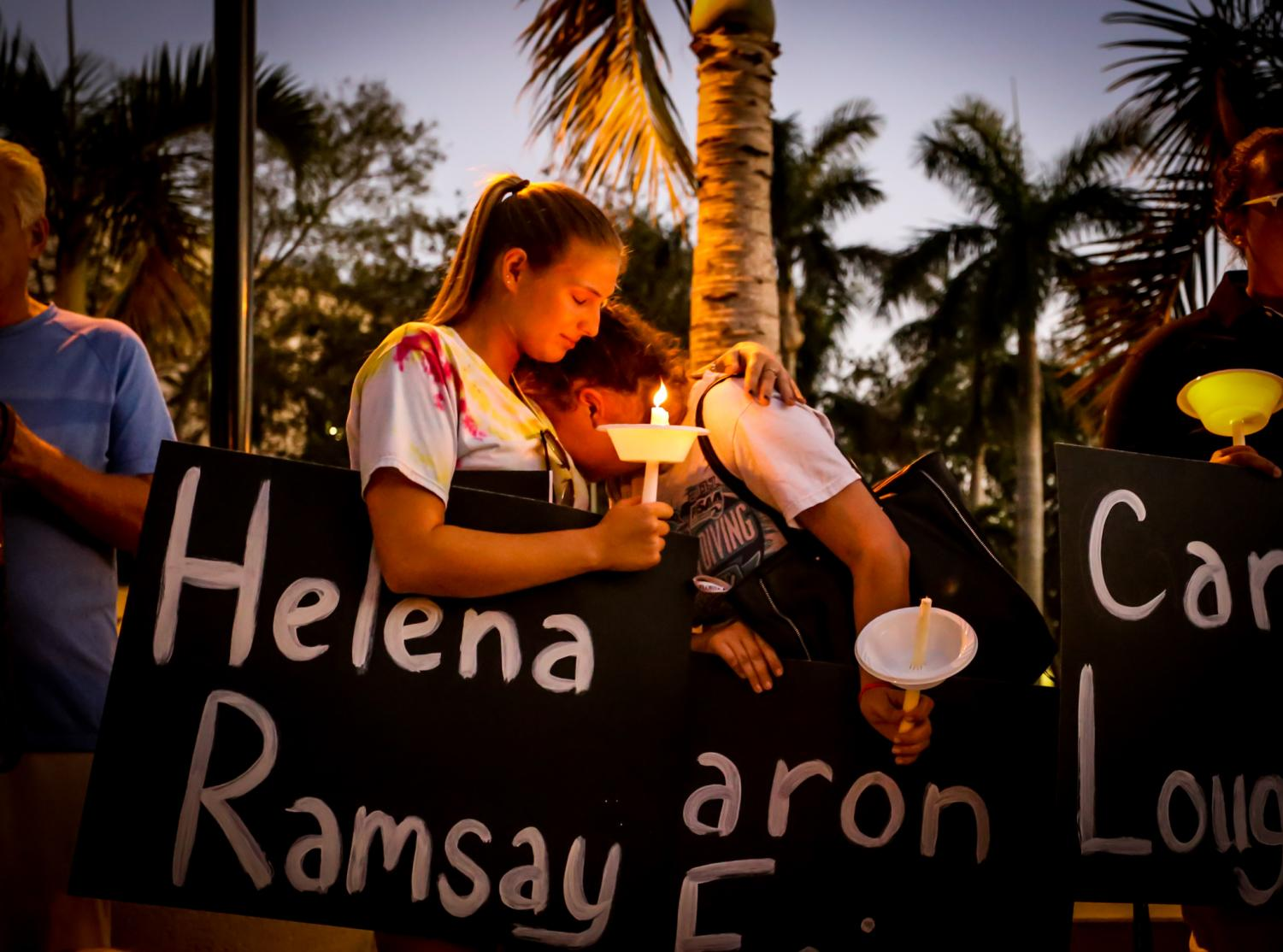 22-year-old graduate student Tori Sletzer, left, holds her friend Taylor Miller, a junior elementary education major, right, during a prayer at the candlelight vigil. Both students attended Marjory Douglas High School and knew the football coach, Aaron Feis, who died shielding other students from gunfire. | Alexander Rodriguez