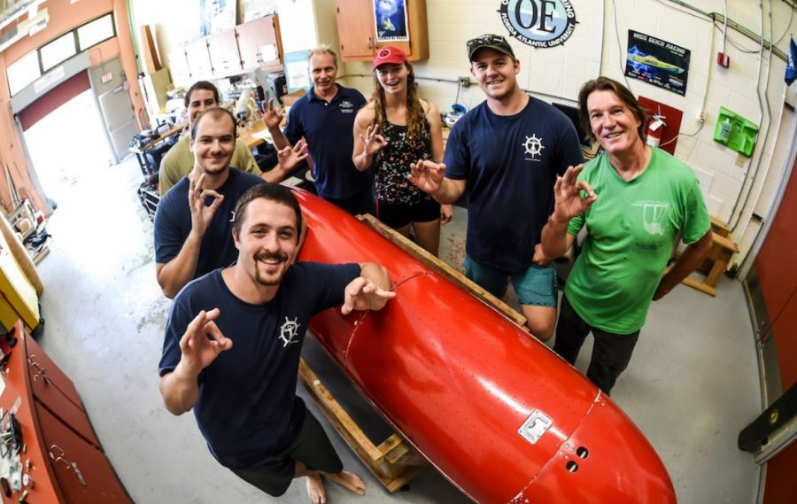 The Human Powered Submarine Club stands with their submarine in their workshop. Photo courtesy of the FAU News Desk