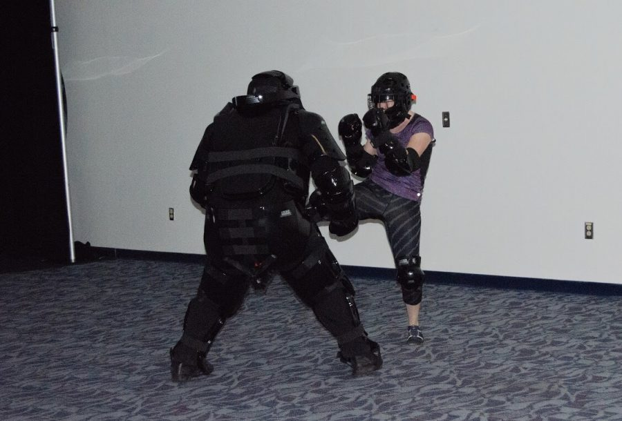 "A participant who attended the Rape Aggression Defense (RAD) program uses her right leg to kick the RAD ""aggressor"" played by an instructor. Photo by Violet Castano"