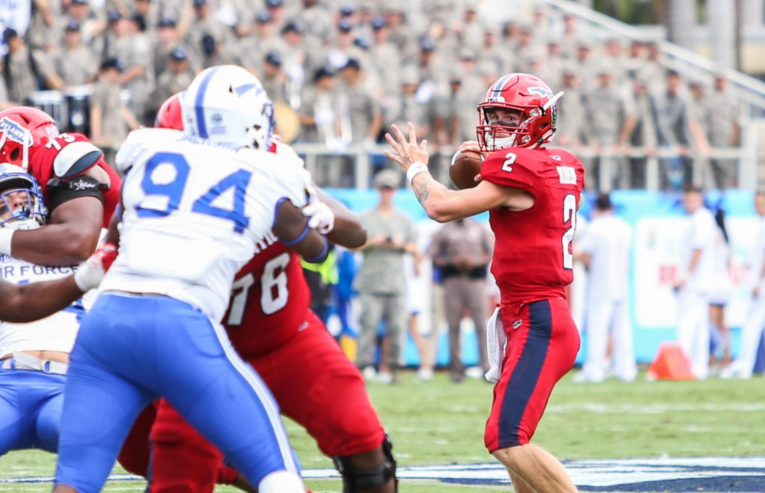 FAU redshirt freshman quarterback Chris Robison (2) decides where to throw the football before being tackled by the Air Force defense. Photo by Alexander Rodriguez