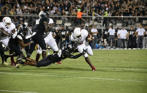 FAU junior running back Devin Singletary (5) attempts to run on the left side before getting tackled by a UCF defensive player. Photo by Pierce Herrmann