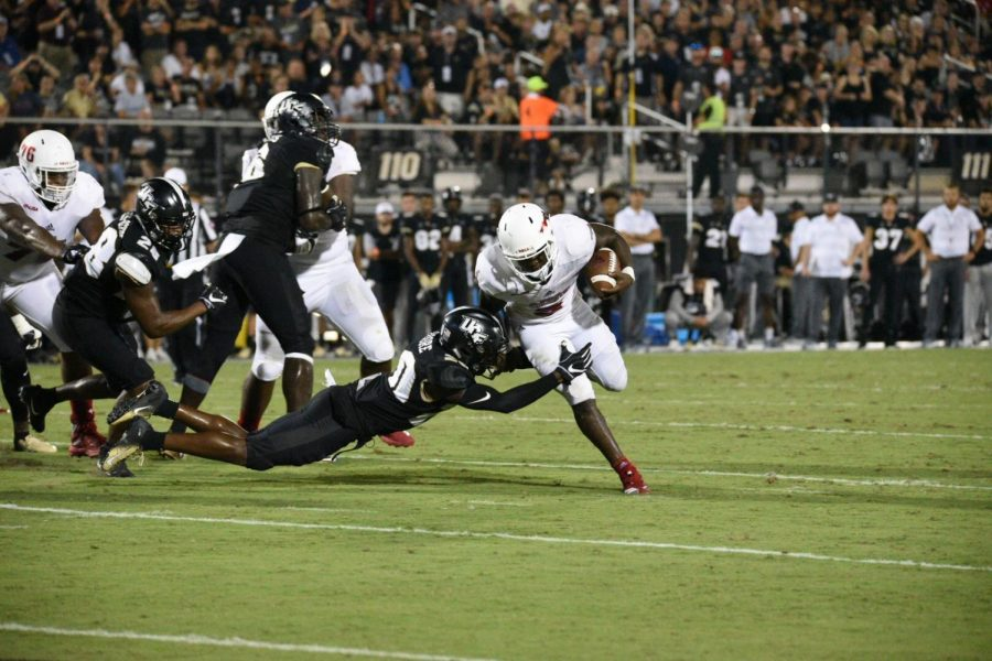 FAU+junior+running+back+Devin+Singletary+%285%29+attempts+to+run+on+the+left+side+before+getting+tackled+by+a+UCF+defensive+player.+Photo+by+Pierce+Herrmann