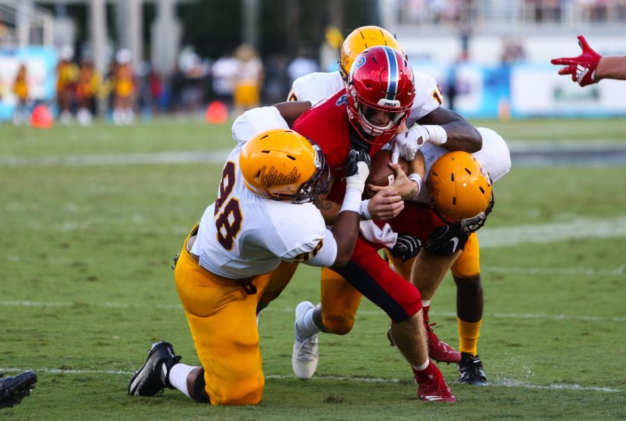 FAU+quarterback+Chris+Robison+%282%29+attempts+to+run+down+the+field+before+getting+tackled+by+three+defensive+Bethune-Cookman+players.+Photo+by%3A+Alexander+Rodriguez%0A