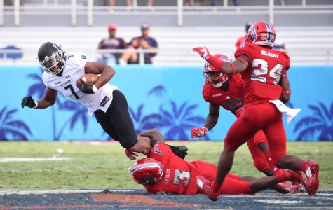FAU senior cornerback Shelton Lewis (3) attempts to tackle and bring down an Old Dominion offensive player. Photo by: Pierce Herrmann