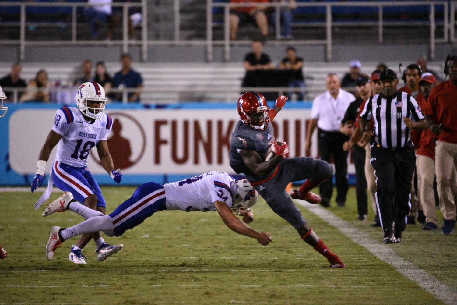 FAU redshirt junior running back Kerrith Whyte Jr. (6) attempts to run down the sideline against LA Tech and narrowly misses getting tackled. Photo by: Pierce Herrmann