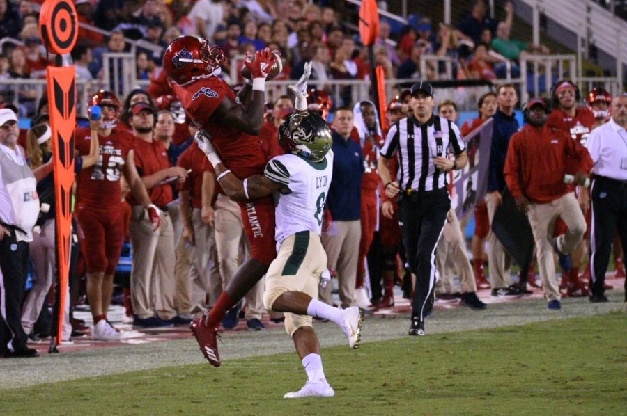 FAU junior wide receiver John Mitchell (85) caught the ball mid air as a Charlotte defensive player tackled him to the ground. Photo by: Pierce Herrmann