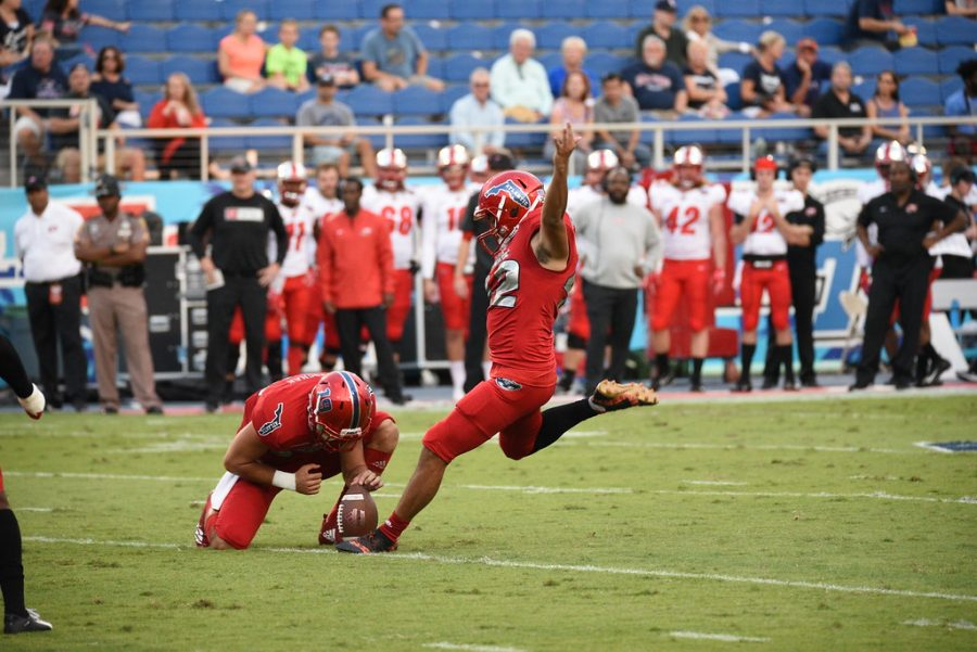 FAU+graduate+student+safety+Jake+Stoshak+%2819%29%2C+left%2C+holds+the+ball+in+place+for+an+attempted+field+goal.+The+field+goal+was+good+and+added+a+point+to+FAU+football+scoreboard+during+the+first+quarter.+Photo+by%3A+Pierce+Herrmann