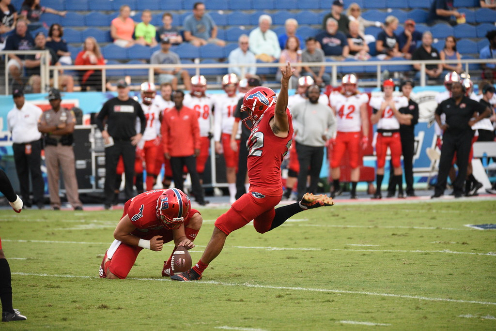 FAU graduate student safety Jake Stoshak (19), left, holds the ball in place for an attempted field goal. The field goal was good and added a point to FAU football scoreboard during the first quarter. Photo by: Pierce Herrmann
