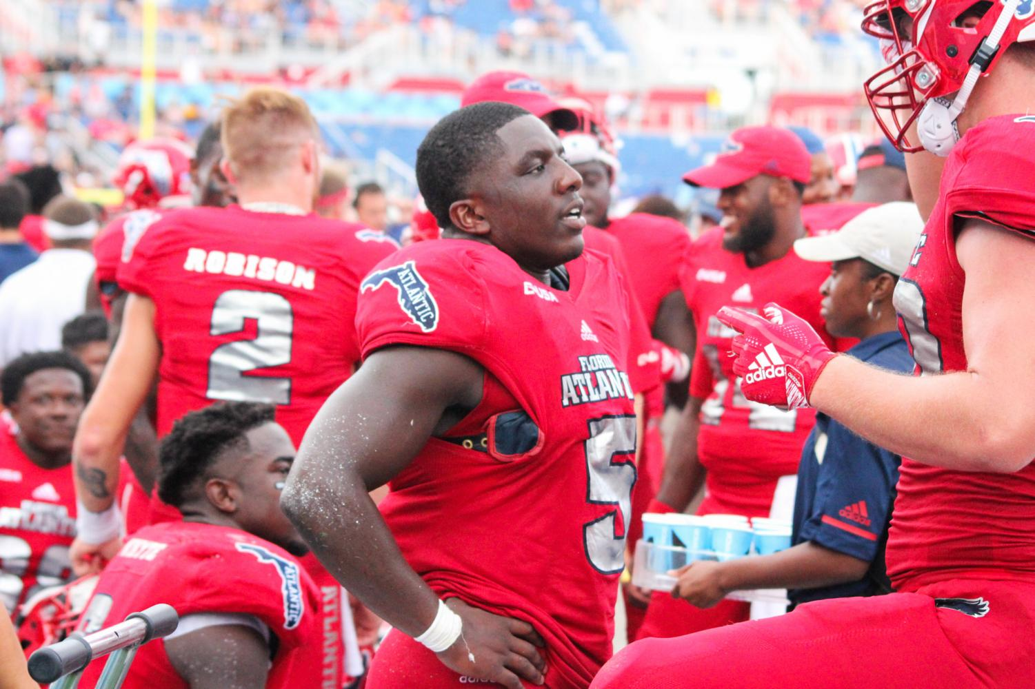 FAU junior running back Devin Singletary (5) talks with his teammates on the sidelines before heading back out to the field. Photo by: Christopher Blackshear
