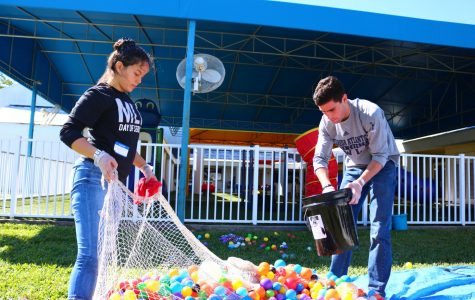 First year graduate student Katherine Aroca (left) and senior John Martin (right) clean the children's ball pit for the first time in a year at Arc Broward. Photo by Brad Casson