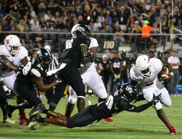 FAU junior running back Devin Singletary (5) attempts to run on the left side before getting tackled by a UCF defensive player. Photo by: Pierce Herrmann