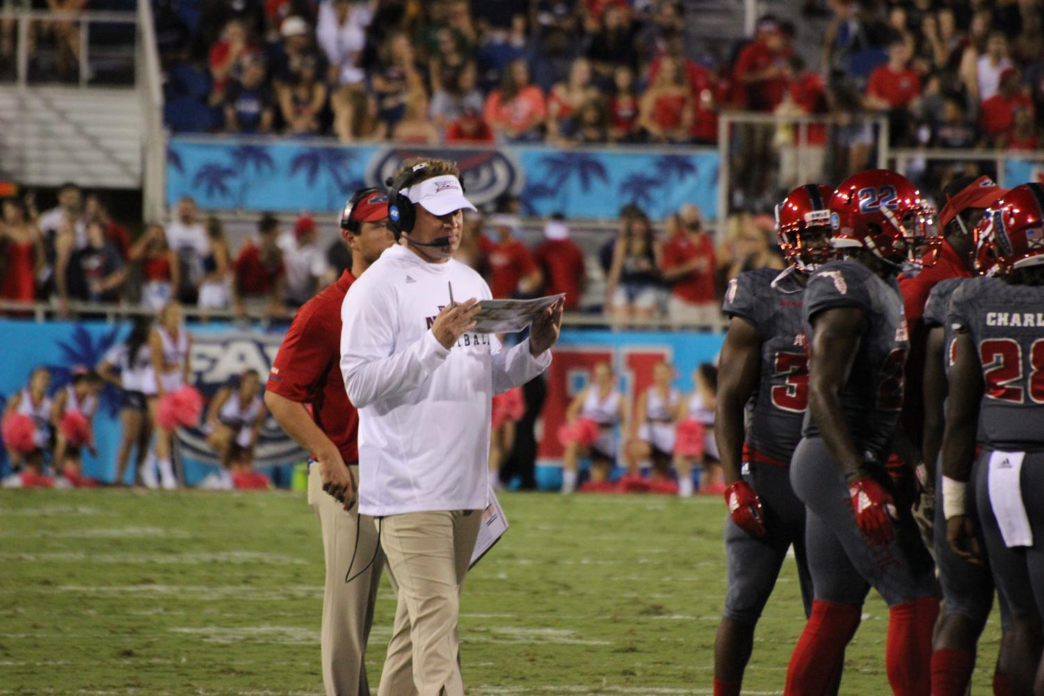 FAU head coach Lane Kiffin goes over plays on his board before speaking with his team. Photo by: Christopher Blackshear