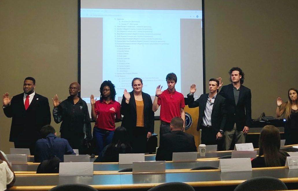 Seven representatives being sworn into the House by Speaker Joshua Rutledge (left).