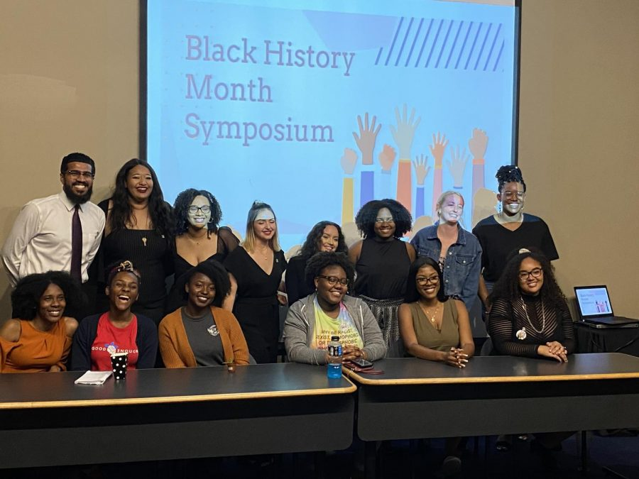 Attendees and panelists who attended the second annual Black History Month Symposium. Left to right standing up: Ryan Daniels, Joi Dean, Sheivon Tribble, Marcela Callejas, Maria Yepes, Ananda Edmonds, Abby Dove, and Simone Stewart. From left to right the panel sitting down: Aleia Dennis, Rachelle Saint-Louis, Naheelah Wallace, Alexa McCalla-Johnson, Arielle Francois, and Lillie Feller. Photo by Destiny Harris