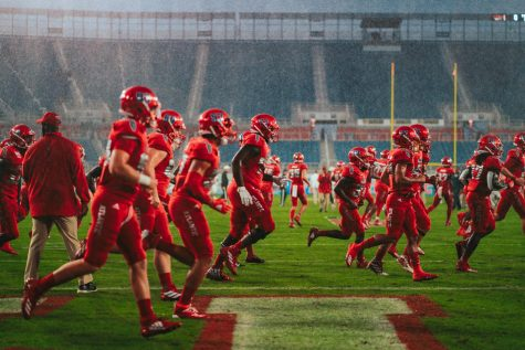 Florida Atlantic Football rushes the field to warm up in the midst of a downpour before the start of the Shula Bowl on Nov. 9, 2019. The Owls beat FIU 37-7. Photo by Alex Liscio.