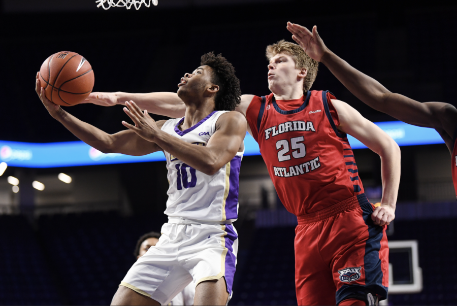 Karlis Silins (numbered 25) contesting a layup against James Madison. Photo courtesy of FAU and JMU Athletics.