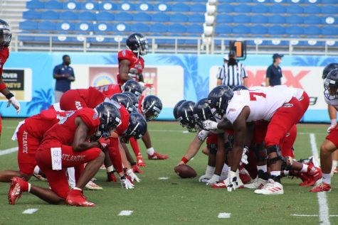 Team Bills (white) gets set to play the ball at the line of scrimmage against Team Perkins (red). Photo by Logan Agostino.