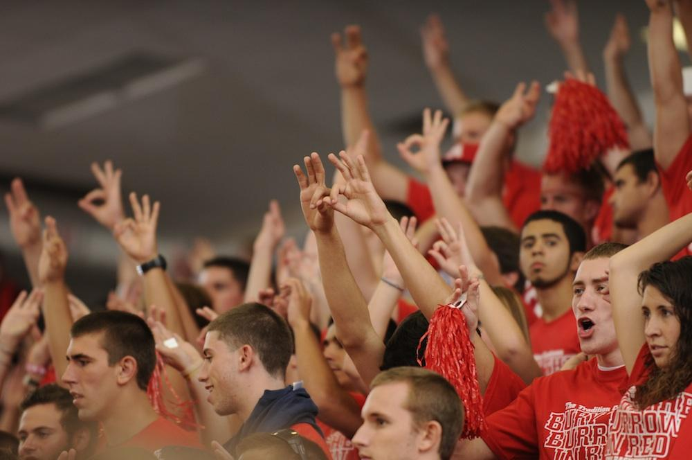 """FAU students show their pride by throwing up the """"Owl Fingers"""" at the """"Bury the Burrow in Red"""" game against FIU on Feb. 5, 2011. Photo by J.C. Ridley"""